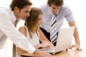 Ein Team bestehend aus einer Frau und zwei Männern sitzen an einem Laptop.