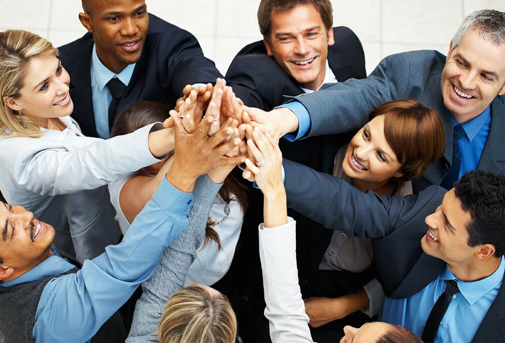 Motivation im Team - Kolleginnen und Kollegen halten die Hände zusammen