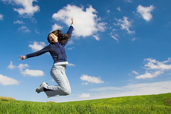 Glücklich sein - Junge Frau hüpft fröhlich in die Luft.