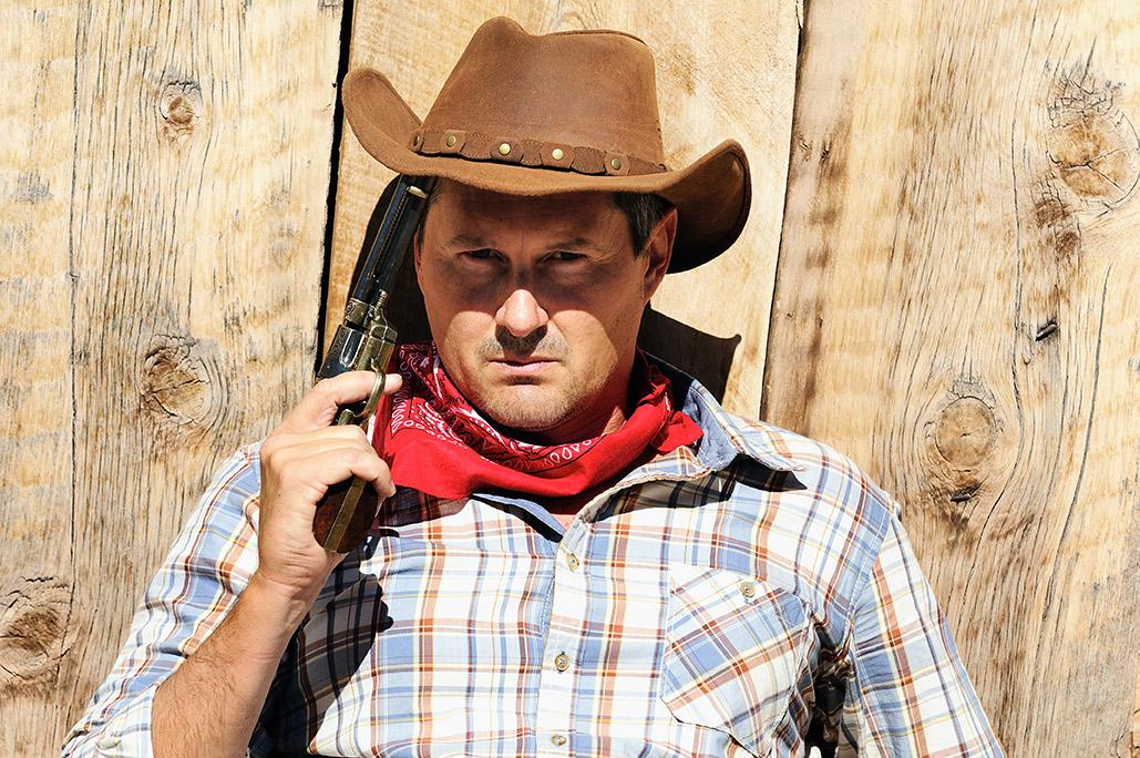Cowboy mit braunem Hut schaut in die Kamera.