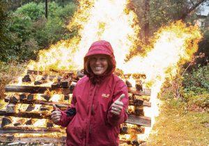 Frau steht vor Feuer und bereitet sich auf den Feuerlauf vor.