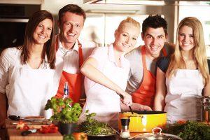 Ein Team kocht gemeinsam mit einem Gourmetkoch