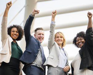 Motivation im Team - ein Team streckt die Arme in die Luft